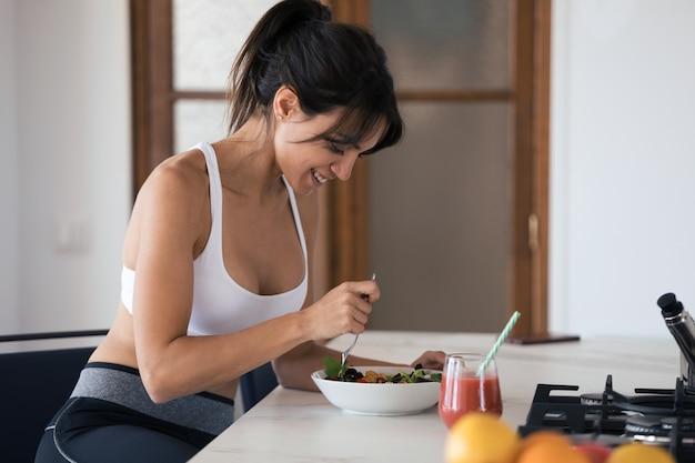Strzał sportowy młoda kobieta jedzenie sałatki i picie soku owocowego w kuchni w domu.