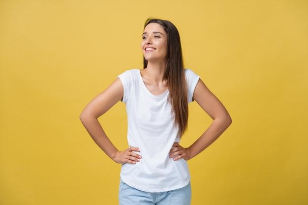 Strzał studio atrakcyjna, pewna siebie, młoda kobieta w świetnym nastroju, czując się szczęśliwa, trzymając się za ręce na jej smukłej talii i patrząc na kamerę z promiennym uśmiechem.