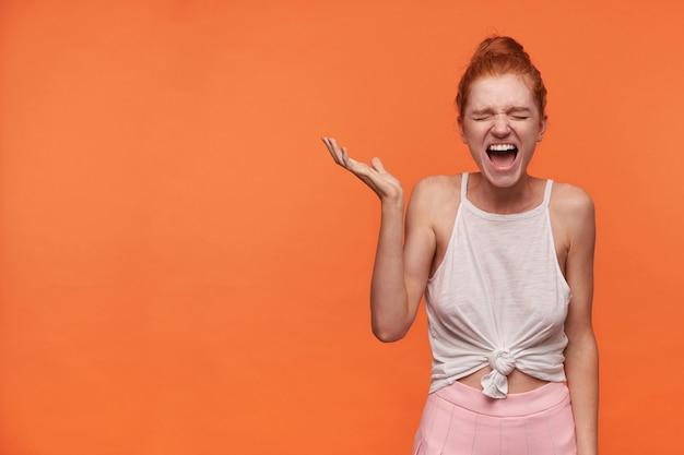 Strzał studio atrakcyjnej młodej kobiety noszącej rude włosy w węzeł pozuje na pomarańczowym tle z uniesioną dłonią, zamykając oczy i krzycząc głośno