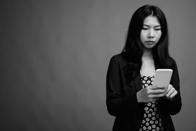 Strzał studio azjatyckiej kobiety korzystającej z telefonu komórkowego na szarym tle w czerni i bieli