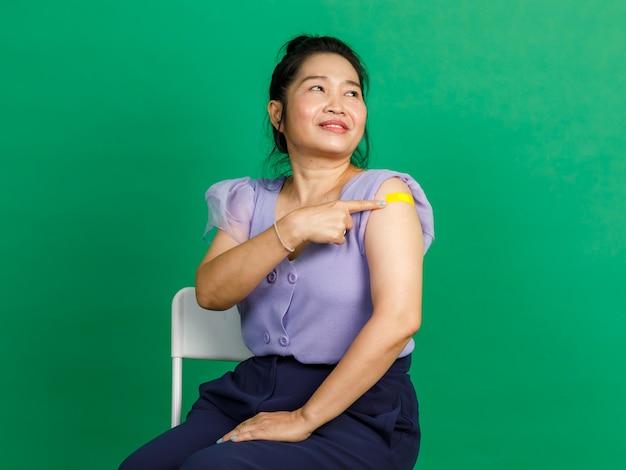 Strzał studio azjatyckiej kobiety w średnim wieku siedzieć uśmiechem wskazując na żółty bandaż na ramieniu po otrzymaniu szczepienia koronawirusa covid 19 przez lekarza w klinice na zielonym tle.
