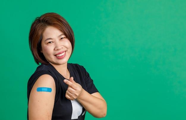 Strzał studio azjatyckiej pacjentki w średnim wieku siedzieć uśmiechem patrzeć na aparat pokaż mini znak ręki serca i bandaż niebieski gips na ramieniu po otrzymaniu szczepienia koronawirusa covid 19 na zielonym tle.