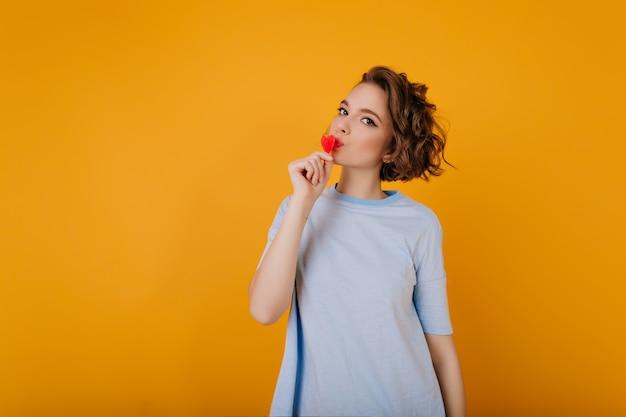 Strzał studio całkiem biała dziewczyna trzyma małe czerwone serce. wewnątrz zdjęcie kobiety z elegancką kręconą fryzurą wychładzającą się przed walentynkami.