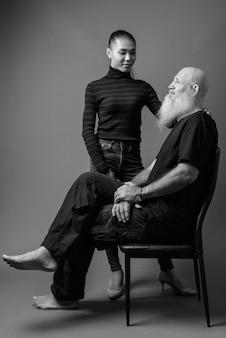 Strzał studio dojrzałego brodatego łysego mężczyzny i młodej pięknej azjatki razem na szarej ścianie w czerni i bieli