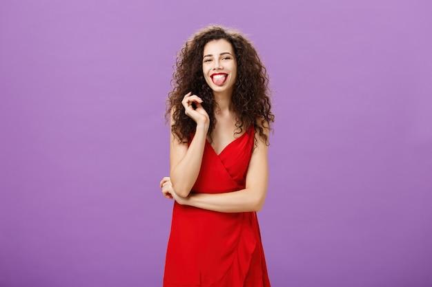 Strzał studio figlarny i radosny artystyczny kaukaski studentka w czerwonej sukni wieczorowej wystający język szczęśliwie bawiący się z curl stojący na fioletowym tle nieostrożny i beztroski.
