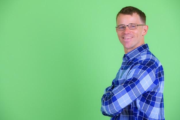 Strzał studio hipster człowieka w okularach na zielonym tle