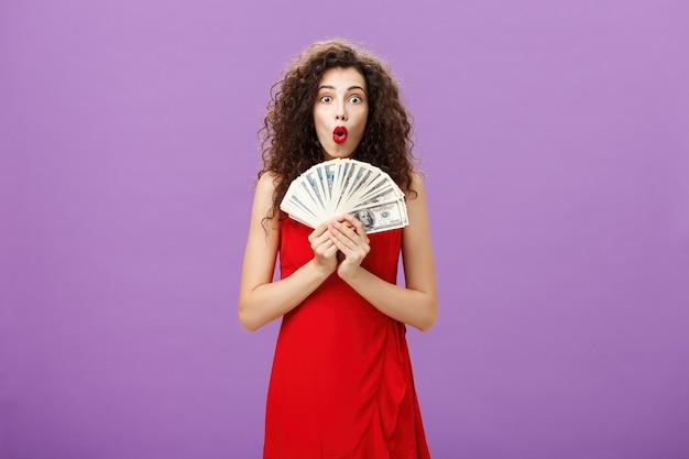 """Strzał studio kobiety, która ma szczęście w kasynie, wygrywając dużo gotówki trzymającej pieniądze w rękach, mówiąc: """"wow"""" z założonymi ustami, patrząc pod wrażeniem i podekscytowana fioletową ścianą w wieczorowej czerwonej sukience."""