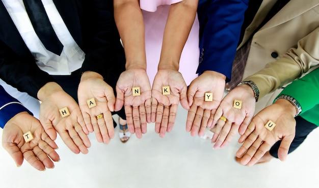 Strzał studio małego drewnianego bloku kostki dziękuję litery alfabetów trzymane w rękach przez nierozpoznawalny niezidentyfikowany personel oficerski bez twarzy w biznesie nosi uznanie dla klientów lub współpracowników.