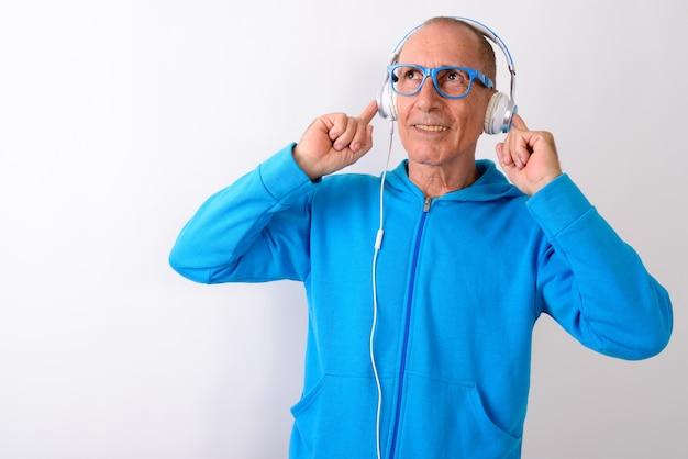 Strzał studio miło szczęśliwy łysy starszy mężczyzna uśmiecha się podczas słuchania muzyki