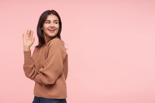 Strzał studio młoda szczęśliwa brunetka kobieta z luźnymi włosami, uśmiechając się radośnie, patrząc przez ramię i trzymając rękę podniesioną, odizolowane na różowej ścianie