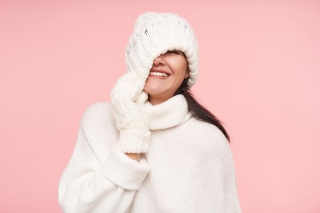 Strzał studio młoda wesoła brunetka kobieta z luźnymi włosami, zdejmując kapelusz i uśmiechając się radośnie, stojąc na różowej ścianie w białych przytulnych ubraniach