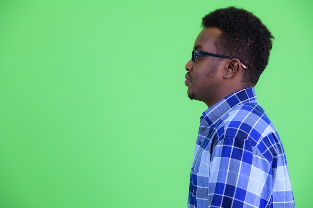 Strzał studio młodego człowieka afrykańskiego hipster z afro włosów, noszenie okularów na zielonym tle