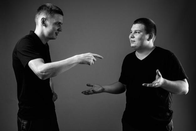 Strzał studio młodego mężczyzny i młodego mężczyzny z nadwagą razem na czarnej ścianie w czerni i bieli