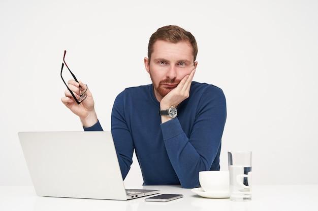 Strzał studio młodego nieogolonego jasnowłosego faceta opierającego brodę na uniesionej dłoni i zmęczonego patrząc na aparat, pozuje na białym tle z okularami w ramieniu