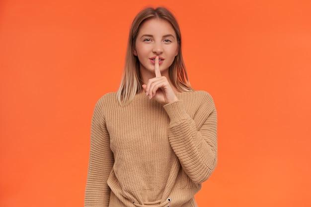 Strzał studio młodej blondynki z krótką fryzurą, która trzyma palec wskazujący na ustach, prosząc o zachowanie jej sekretu i przebiegle uśmiechnięta, odizolowana na pomarańczowej ścianie