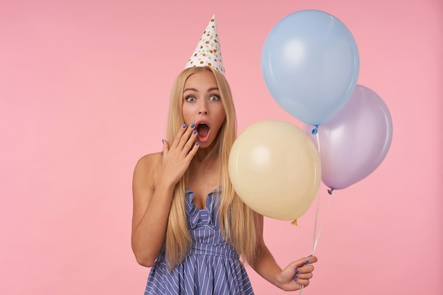 Strzał studio młodej kobiety długowłosej w świątecznych ubraniach i kapeluszu w kształcie stożka, trzymającej kilka balonów z helem, pozując na różowym tle, patrząc na aparat z zaskoczeniem i zakrywając usta dłonią