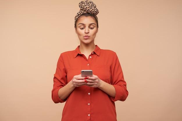 Strzał studio młodej ładnej brązowowłosej kobiety noszącej pałąk w węzeł podczas pozowania nad beżową ścianą, trzymając smartfon w uniesionych rękach i wydrążając usta, patrząc na ekran