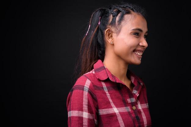 Strzał studio młodej pięknej kobiety azjatyckich hipster z plecionych włosów na czarnym tle