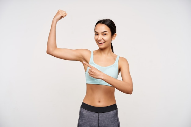 Strzał studio młodej wesołej sportowej brązowowłosej kobiety uśmiechającej się przyjemnie, wskazując z radością na jej podniesioną rękę palcem wskazującym, odizolowanej na białej ścianie