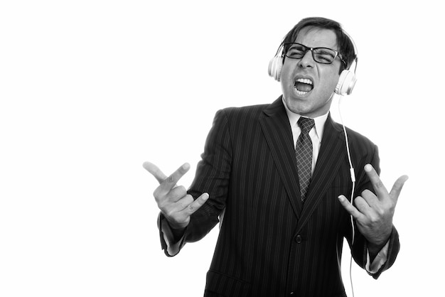 Strzał studio młody biznesmen perski, słuchanie muzyki z gestem ręki rocka na białym tle