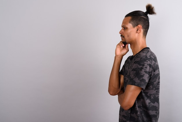 Strzał studio młody brodaty przystojny mężczyzna afryki na sobie koszulę z nadrukiem kamuflażu z włosami związanymi na szarym tle