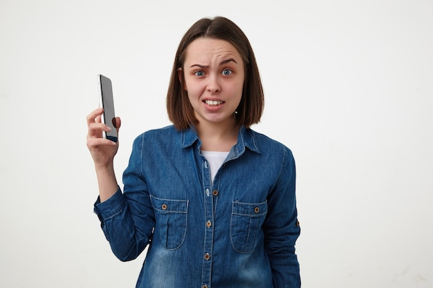 Strzał studio oszołomionej młodej brunetki kobiety, która niepewnie podnosi brwi, patrząc na aparat i podnosząc rękę ze smartfonem w nim, na białym tle nad białym