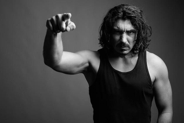Strzał studio przystojnego mężczyzny macho z kręconymi włosami i wąsami na szarym tle w czerni i bieli
