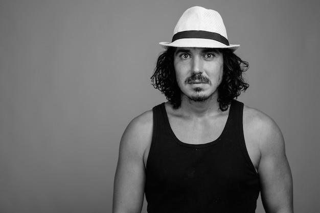 Strzał studio przystojny turysta mężczyzna z kręconymi włosami i wąsami na szarym tle w czerni i bieli
