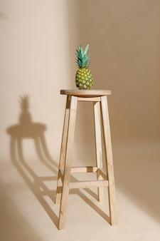 Strzał studio świeżych i słodkich całych owoców ananasa z liściem na krześle na białym tle nad beżem