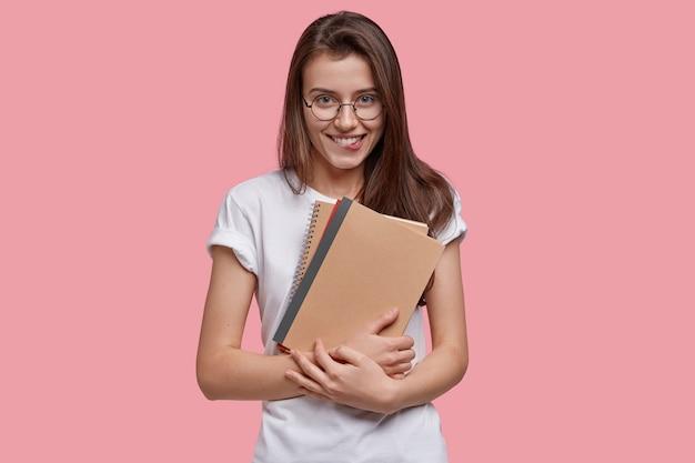 Strzał studio szczęśliwa nastolatka gryzie dolną wargę, nosi notesy, wygląda radośnie, nosi białą koszulkę, okrągłe okulary