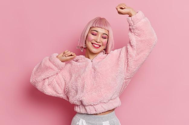 Strzał studio wesoła młoda ładna azjatka nosi różową perukę jasny makijaż podnosi ramiona czuje optymistyczny taniec beztroski świętuje coś ubranego w futro