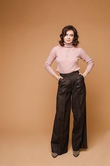 Strzał studio wspaniałej modnej brunetki z falowanymi włosami. modelka w eleganckim ubraniu - jasnoróżowy sweter i ciemnobrązowe spodnie. pozowanie z rękami w kieszeniach.