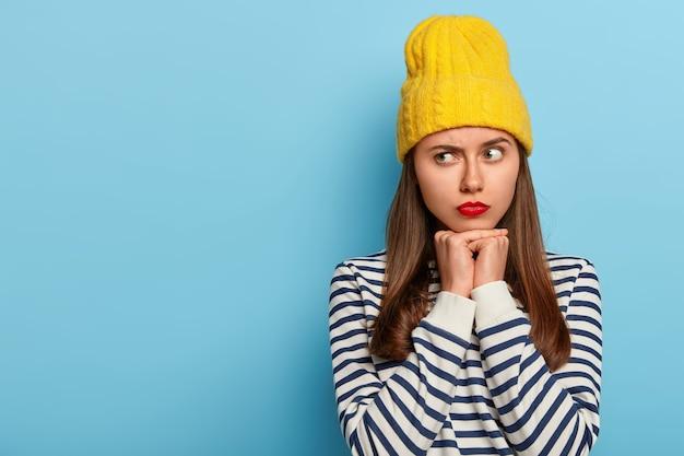 Strzał studio zamyślonej młodej modelki wygląda na bok z poważną miną, ubrana w sweter w paski, żółty stylowy kapelusz, odizolowany na niebieskim tle, puste miejsce na promocję