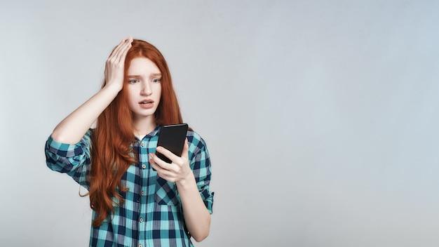 Strzał studio zszokowanej rudej kobiety w casual, trzymając rękę na głowie i patrząc na telefon komórkowy, stojąc na szarym tle. negatywne emocje. cyfrowy