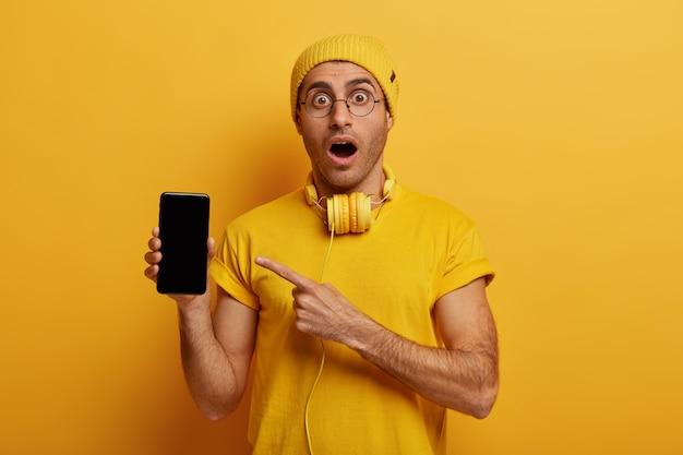 Strzał studio zszokowany młody człowiek wskazuje na wyświetlacz smartfona, pokazuje czarny ekran, pokazuje nowoczesny produkt