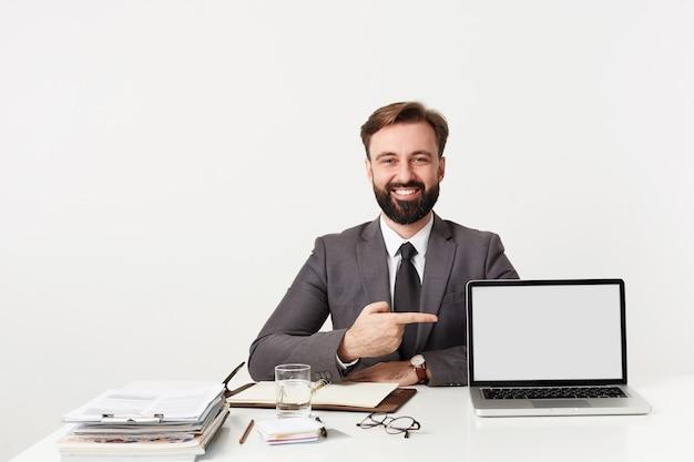 Strzał szczęśliwy młody biznesmen brunetka z brodą, ubrany w szary garnitur i krawat, siedząc przy stole roboczym z laptopem, wskazując na ekranie i uśmiechając się radośnie, odizolowany na białej ścianie