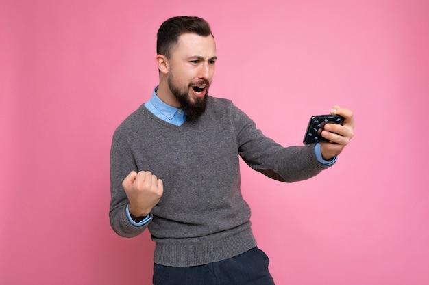 Strzał szczęśliwy przystojny młody brunetka nieogolony mężczyzna z brodą ubrany codziennie szary sweter i niebieską koszulę na białym tle na tle ściany trzymając smartfon grający w gry przez telefon komórkowy, patrząc na phon