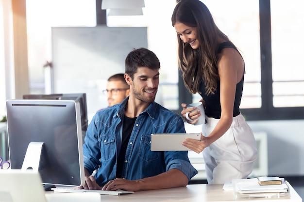 Strzał udanej młodej pary biznesu, współpracującej z cyfrowym tabletem w nowoczesnym biurze startowym.