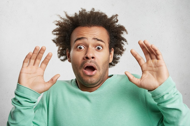 Strzał w głowę młodego mężczyzny rasy mieszanej z fryzurą afro, oszołomiony przerażonym wyrazem twarzy, unosi dłonie i mówi: