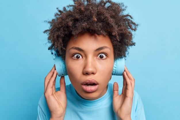 Strzał w głowę pod wrażeniem oszołomionej kręconej kobiety z wytrzeszczonymi oczami utrzymuje oddech słucha muzyki w bezprzewodowych słuchawkach zszokowany, gdy niespodziewanie słyszy bardzo głośny dźwięk na niebieskiej ścianie