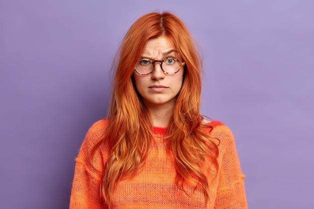 Strzał w głowę wściekłej rudej kobiety wygląda na niezadowoloną, unosi brwi i słyszy zdziwione wiadomości, nosi przezroczyste okulary i pomarańczowy sweter.