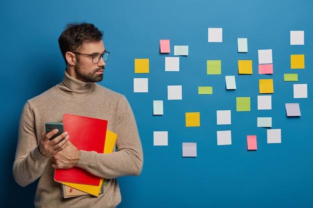 Strzał w górę brodaty mężczyzna ma kreatywne myślenie, kolorowe notesy przyklejone do niebieskiej ściany, trzyma spiralny notatnik
