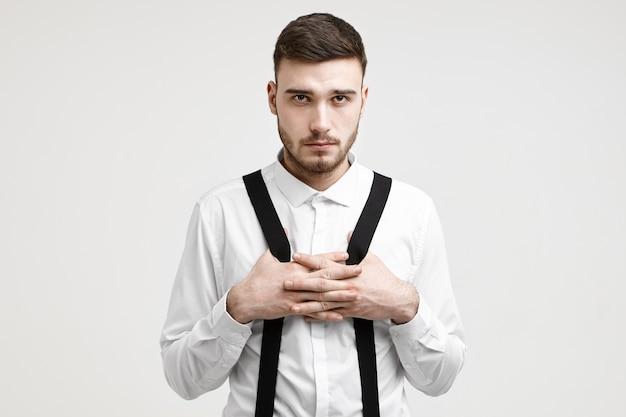 Strzał w górę poważnego, pewnego siebie młodego europejczyka typu macho z włosiem stojącego na tle białej ściany studia, ubranego w formalną koszulę, krzyżującego ręce na piersi, ciągnącego szelki