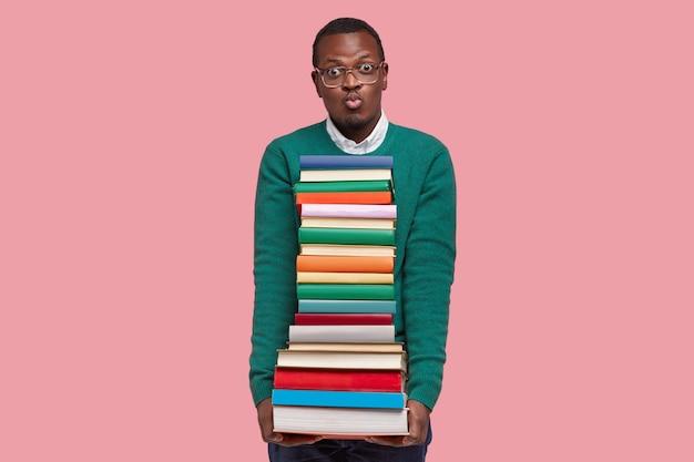 Strzał w górę przystojnego czarnego mężczyzny wydyma usta, nosi podręczniki, krzywi się do kamery, nosi zielony sweter, modele na różowej ścianie