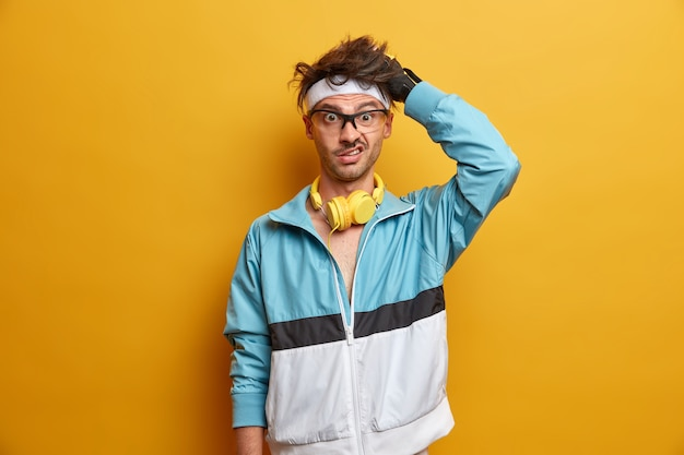 Strzał w górę sportowca drapie głowę i wygląda na zdziwionego, uprawia sport w domowej siłowni, nosi słuchawki na szyi, ćwiczenia z trenerem, ubrany w odzież sportową, odizolowany na żółtej ścianie