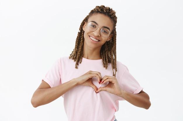 Strzał w górę uroczej, atrakcyjnej i przyjaznej dziewczyny afroamerykanów z dreadami w różowej koszulce pokazującej gest serca