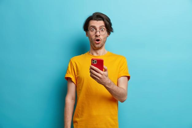Strzał w górę zaskoczony facet hipster reaguje emocjonalnie na szokujące wiadomości trzyma telefon komórkowy