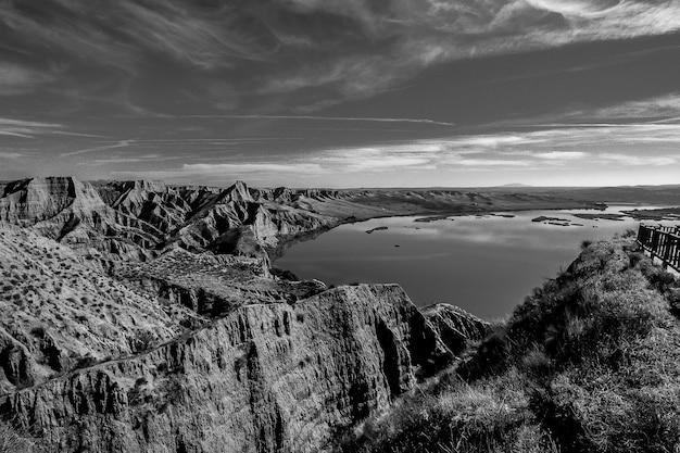 Strzał w skali szarości gór w pobliżu jeziora w burujon, hiszpania