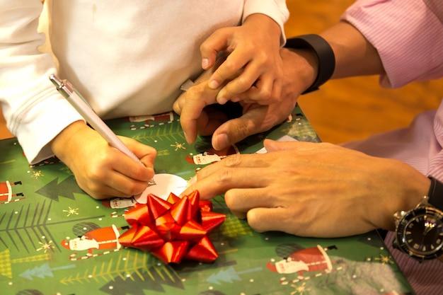 Strzał w słabym świetle młody chłopak pisze kartkę świąteczną z ojcem