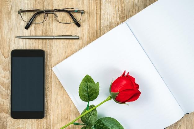 Strzał widok z góry czerwonych róż pusty notatnik pusty pamiętnik i okulary z smartphone na drewnianym stole, koncepcja valentine
